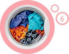 ubrania w pralce wewnątrz różowego obramowania z cyfrą 6